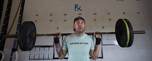 Reymundo Zapata, who had partial knee replacement surgery in April, does squats during a CrossFit workout at Armor Of God Fitness in Gregory